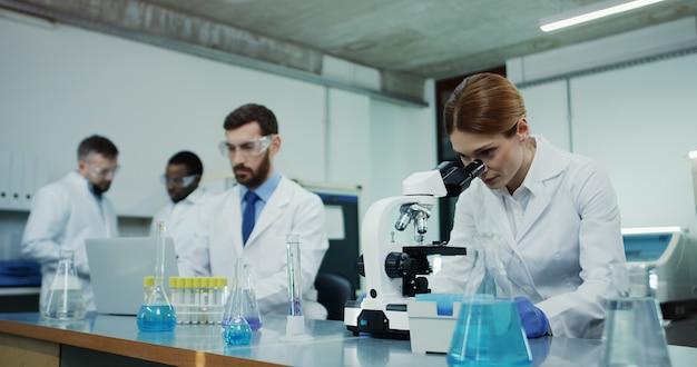 Cientista de mulher caucasiana com a túnica branca, olhando no microscópio enquanto fazia alguma investigação e seu colega masculino testando algum líquido no tubo no computador portátil.