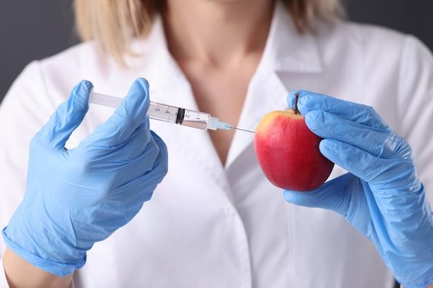 Cientista de mulher em luvas de borracha, fazendo injeção na apple closeup. engenharia genética