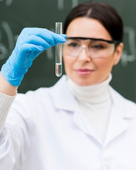 Cientista de mulher olhando para tubo de laboratório