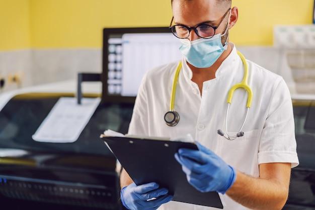 Cientista de pé no laboratório e segurando os resultados dos testes nas mãos.
