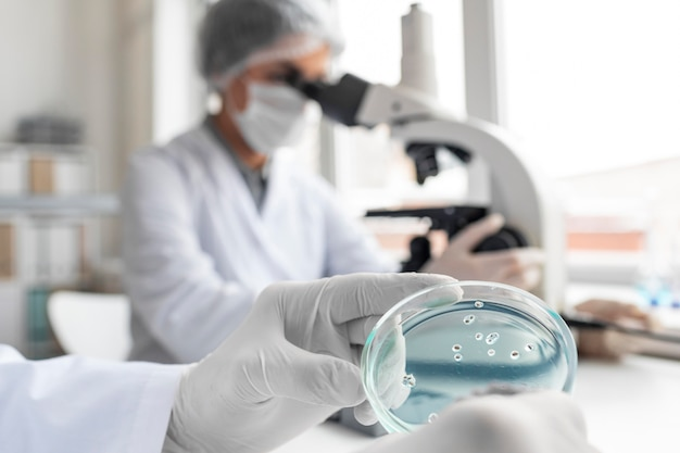 Cientista de perto usando microscópio