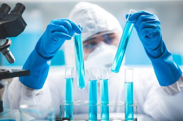 Cientista de pesquisadores trabalhando análise com tubo de ensaio de líquido azul no laboratório, ciência química ou tecnologia de experimento de biologia médica, solução de desenvolvimento de farmácia