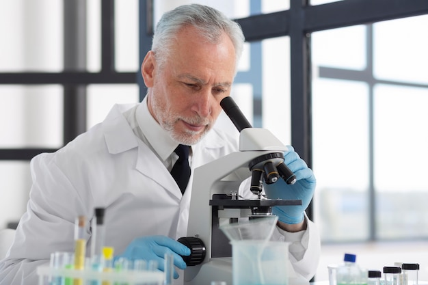 Cientista de tiro médio olhando através do microscópio