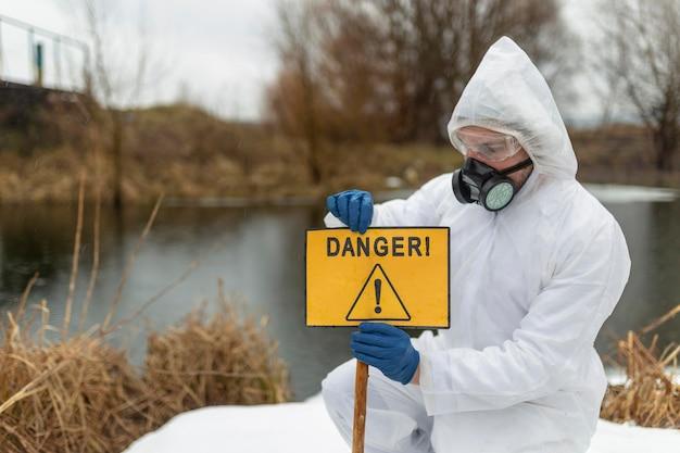 Cientista de tiro médio segurando placa de perigo