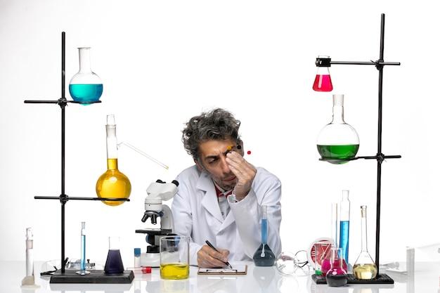 Cientista de visão frontal sentado em frente à mesa pensando em soluções