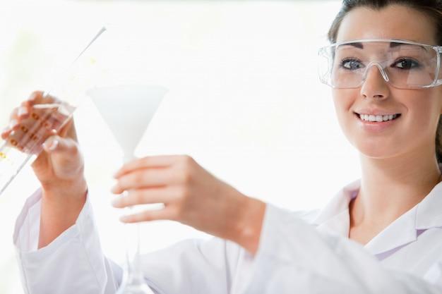 Cientista derramando líquido com um funil