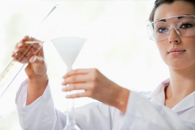 Cientista derramando líquido em um funil