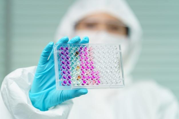 Cientista em laboratório com tubo biológico para análise e amostragem de covid-19.
