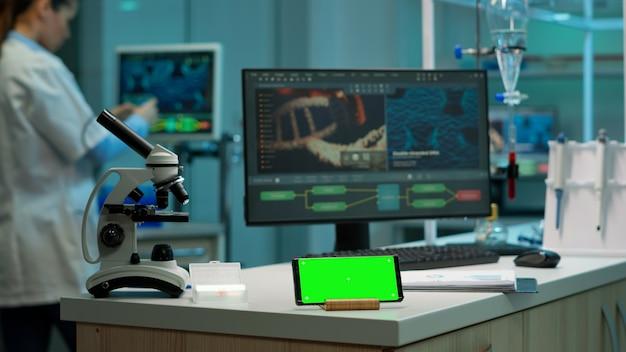 Cientista em pé no monitor em segundo plano, analisando a evolução do vírus enquanto o telefone com tela verde maquete trabalha na frente. mulher pesquisadora de laboratório examinando desenvolvimento de vacina e trazendo amostras de sangue