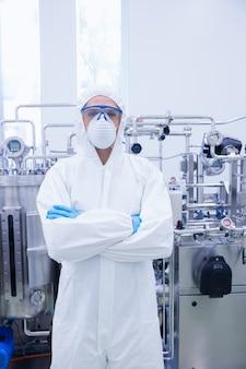Cientista em terno protetor de pé com os braços cruzados