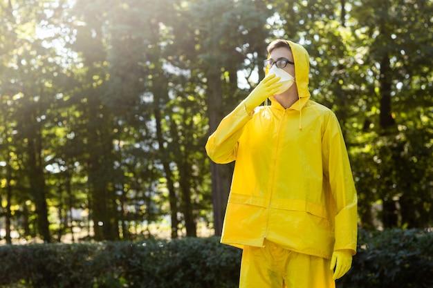 Cientista em traje de proteção amarelo, óculos e respirador.