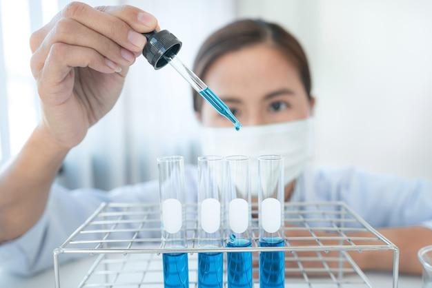 Cientista em um conta-gotas médico segurando para jogar um líquido químico em um tubo de ensaio e ver a reação