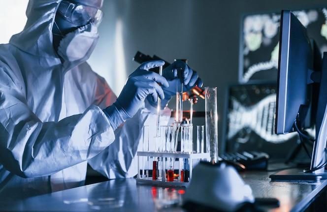 Cientista em uniforme de proteção branco trabalha com coronavírus e tubos de sangue em laboratório
