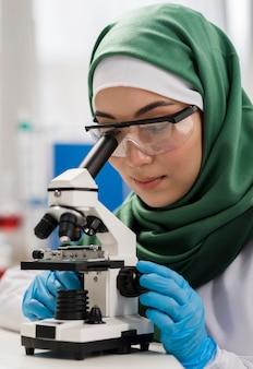 Cientista fêmea com hijab e microscópio no laboratório