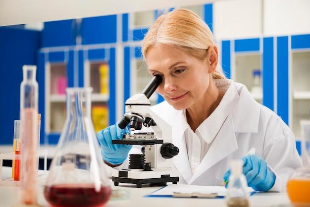 Cientista fêmea com luvas cirúrgicas, olhando através do microscópio