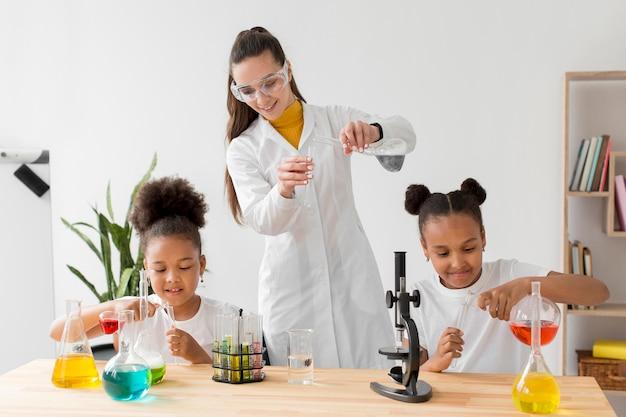Cientista fêmea ensinando jovens meninas experiências de química
