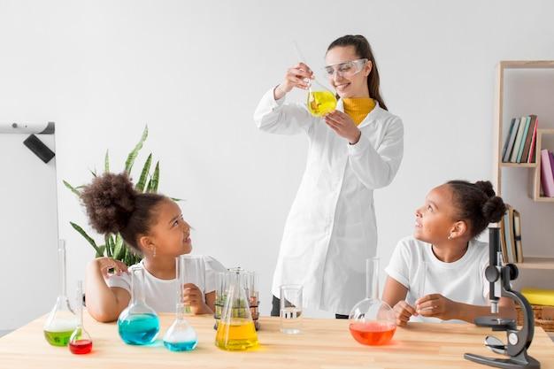Cientista fêmea ensinando química de meninas enquanto segura o tubo com poção