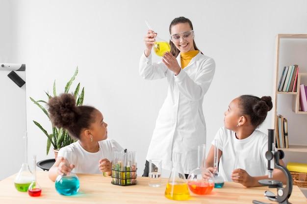 Cientista fêmea ensinando química de meninas enquanto segura o tubo