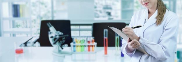 Cientista fêmea escreve uma nota curta e trabalhando em laboratório