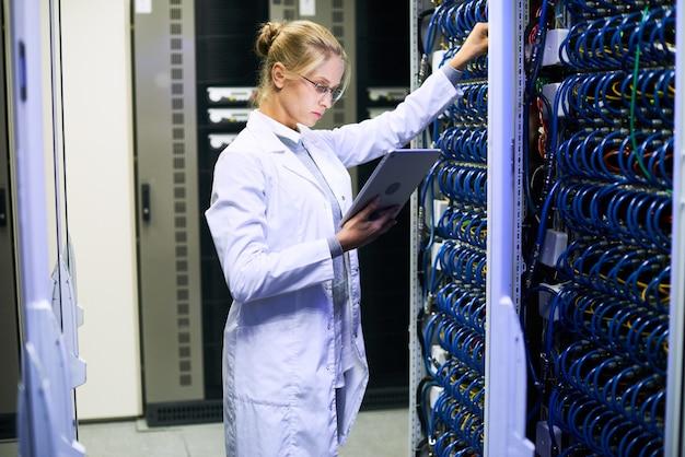 Cientista fêmea que trabalha com servidores