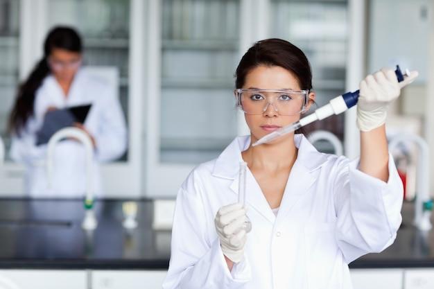 Cientista fêmea séria que derrama um líquido em um tubo