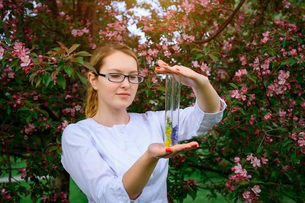 Cientista feminina de óculos e jaleco branco com tubos de ensaio nas mãos estuda as propriedades das plantas no jardim botânico. criando aromas florais, cosméticos naturais, fitoterapia, perfumes.