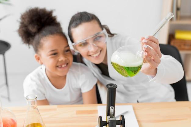 Cientista feminina e garota se divertindo com experimentos de química