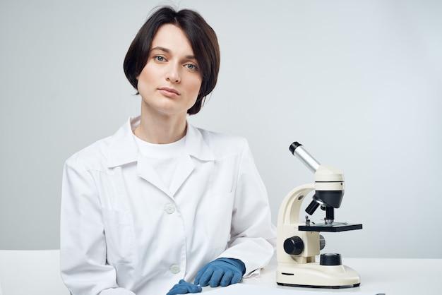 Cientista feminina em experimento científico de microscópio de laboratório de jaleco branco