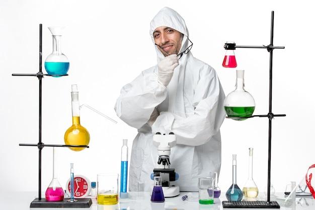 Cientista frontal do sexo masculino em traje de proteção especial em pé ao redor da mesa com soluções