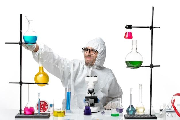 Cientista frontal do sexo masculino em traje de proteção especial sentado ao redor da mesa com soluções