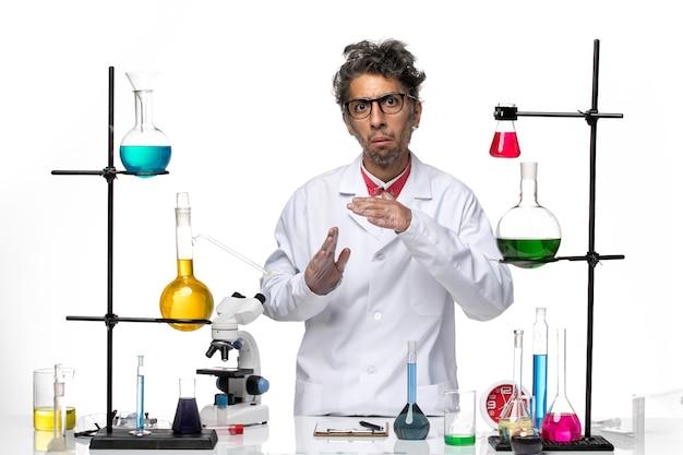 Cientista frontal em traje médico branco em frente à mesa com soluções