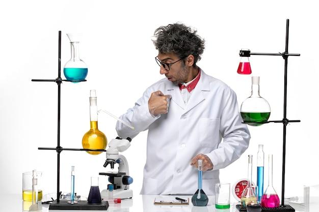 Cientista frontal em traje médico branco, em pé e olhando para algo