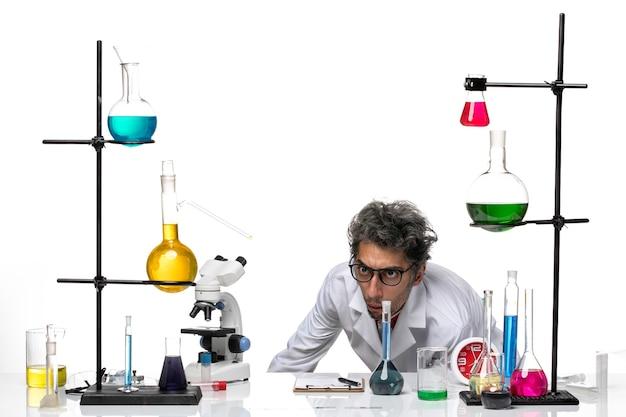 Cientista frontal em traje médico branco, olhando para algo