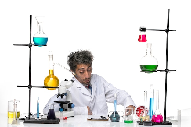 Cientista frontal em traje médico branco sentado com soluções