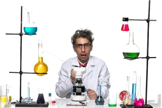 Cientista frontal em traje médico branco sentado com uma expressão confusa