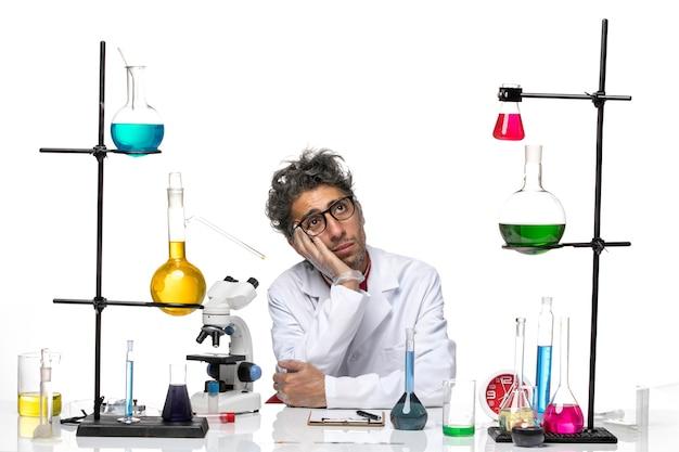 Cientista frontal em traje médico branco sentado e sonhando
