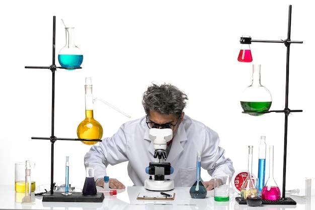 Cientista frontal em traje médico branco usando microscópio