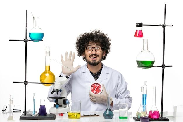 Cientista frontal em traje médico, segurando relógios vermelhos e acenando no espaço em branco