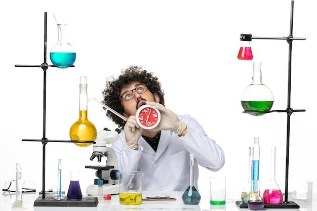 Cientista frontal em traje médico segurando relógios vermelhos na mesa branca.