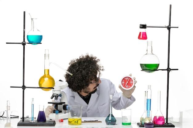 Cientista frontal em traje médico segurando relógios vermelhos na mesa branca