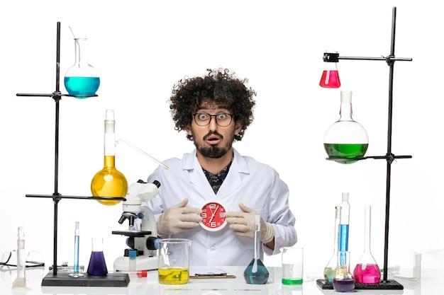 Cientista frontal em traje médico segurando relógios vermelhos no espaço em branco