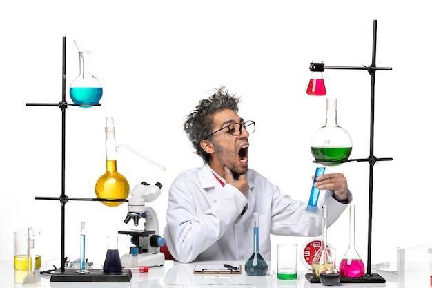 Cientista frontal masculino em traje médico branco trabalhando com soluções