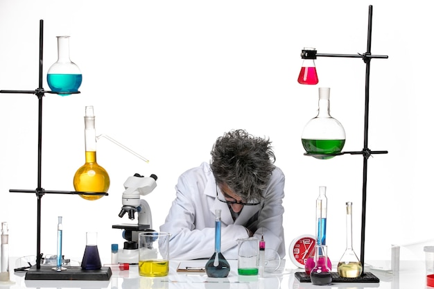 Cientista frontal masculino em traje médico trabalhando com soluções