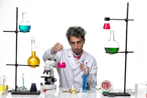 Cientista frontal segurando amostras e solução em fundo branco coronavirus laboratório de saúde covid