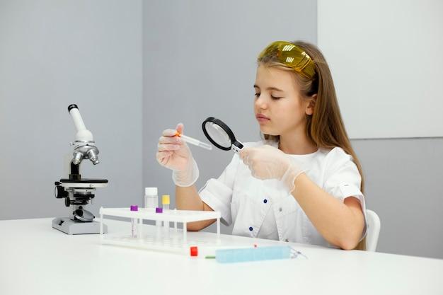 Cientista garota com óculos de segurança e microscópio