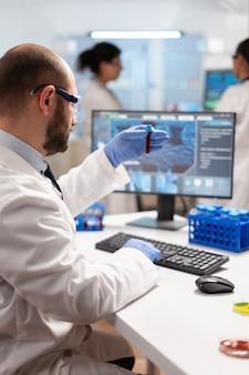 Cientista genético estuda epidemias segurando amostra de sangue