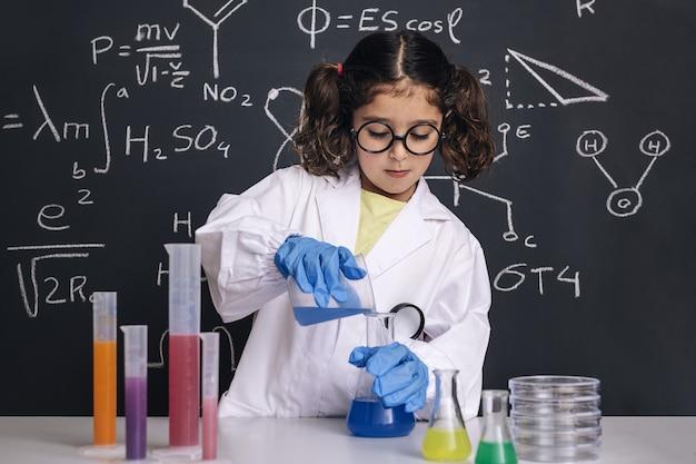 Cientista infantil com luvas misturando líquidos químicos