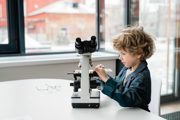 Cientista inteligente colocando uma amostra química no microscópio enquanto vai estudar novos elementos em laboratório