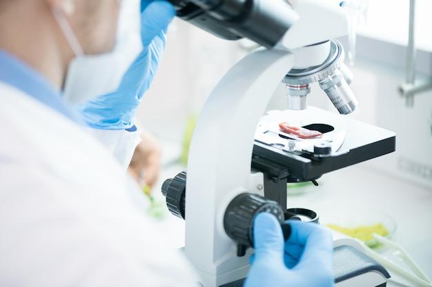 Cientista irreconhecível usando microscópio