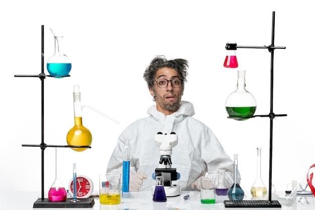 Cientista louco de visão frontal em traje de proteção especial, sentado ao redor da mesa com soluções sobre fundo branco claro, doença de laboratório covid- vírus da ciência